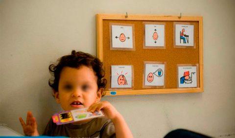 Garotinha, em primeiro plano, segurando uma caixa, e, ao fundo, um quadro, com seis figuras, representando atividades diárias
