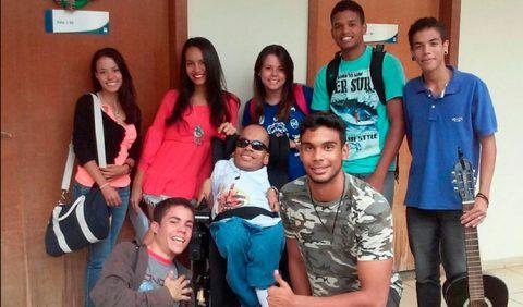 Um rapaz em cadeira de rodas ao centro, rodeado por três meninas, atrás dele, e dois quatro rapazes