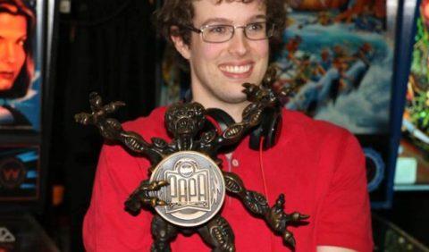 Jovem autista, sorrindo, com um trofeu a sua frente