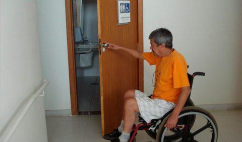 Homem em uma cadeira de rodas abre a porta de um banheiro