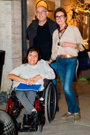 Três pessoas - uma mulher em uma cadeira de rodas, no primeiro plano, e um casal, de pé, atrás dela