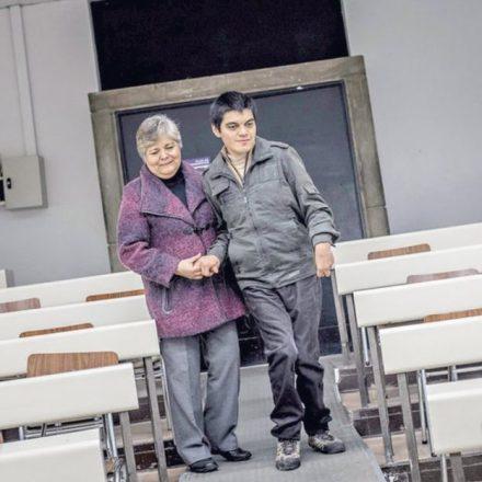Uma senhora de cabelos brancos auxilia um jovem com deficiência a caminhar em uma sala de aula, segurando sua mão e enlaçando sua cintura