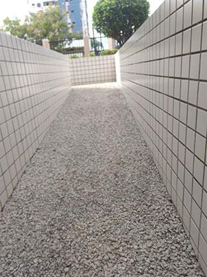Foto de uma rampa de pedrinhas e, nas laterais, paredes com pequenos azulejos brancos