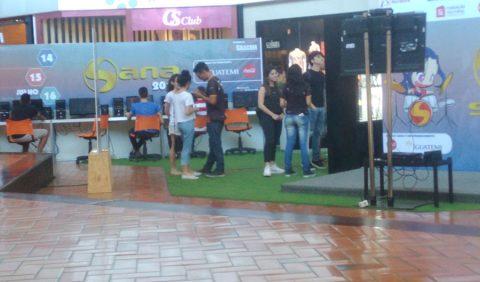 Visão frontal da praça de exposições do Shopping Iguatemi, com o nome Sana 2017 à esquerda em um grande banner, pessoas conversando e jogando vídeo game