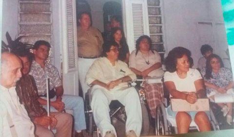 Foto antiga, meio desbotada, mostrando onze pessoas na varanda de uma casa