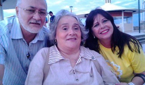 Três pessoas, lado a lado, sorrindo. Um homem de barba branca à esquerda, uma mulher ao centro, de cabelos brancos, e uma mulher jovem à direita.