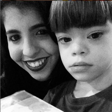 Foto em preto e branco de uma jovem e seu irmão com Síndrome de Down