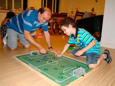 Um homem e um menino ajoelhados no chão, brincando de futebol de botão em um campo miniatura