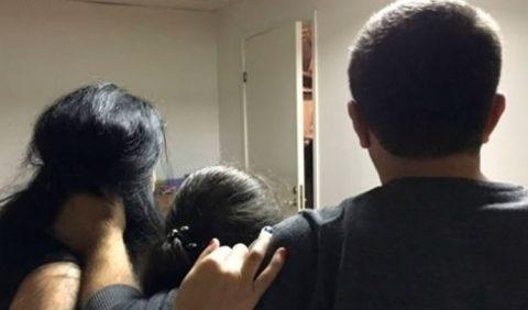Três pessoas de costas - uma mulher à esquerda, uma garotinha ao centro e um homem à direita - olhando para uma parede branca