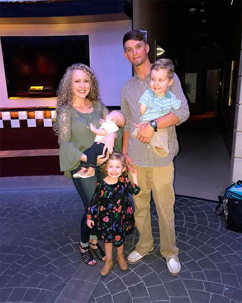Kate Whiddon segura seu bebê Jaxton no colo e, ao seu lado, o marido Cole Green segura o pequeno Camden. Ryleign sorri, segurando a mão do pai.
