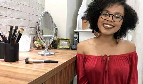Uma moça negra, jovem, sorrindo, usando uma blusa cigana vermelha, de óculos e, do seu lado direito, uma bancada com várias produtos de maquiagem, um espelho e um telefone