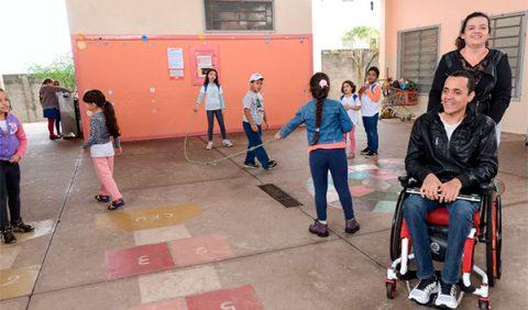 Pátio de uma escola com uma mulher empurrando uma cadeira de rodas com um homem sentado e, ao fundo, crianças brincam de pular corda, conversam e bebem água no bebedouro