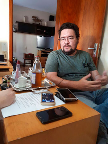 Foto vertical com um homem à direita, de óculos, barba, blusa verde e calça jeans; à esquerda, uma mesa com uma bandeja com uma garrafa, copos e xícaras, celulares, papel e uma mão