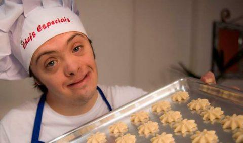 Garoto com Síndrome de Down, vestido de cozinheiro, segurando uma travessa de biscoitos em forma de estrelas
