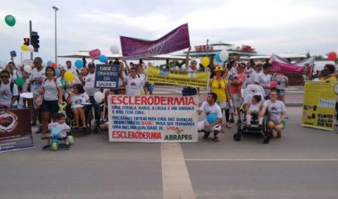 Grupo de pessoas - homens, mulheres e crianças - carregando faixas e usando camisetas alusivas ao Dia Mundial das Doenças Raras
