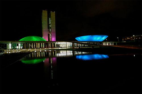 Foto escura das cúpulas do Congresso Nacional iluminadas de verde, azul, rosa e roxo