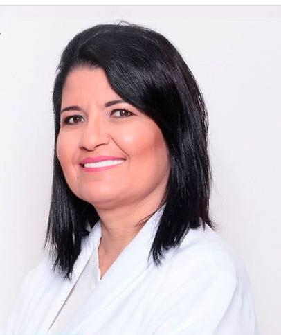 Foto de uma mulher sorrindo, de lado, até a altura dos cotovelos, com uma roupa branca e fundo também branco