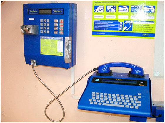 Foto quadrada de um telefone público azul de parede conectado a um outro aparelho também azul chamado teletipo, semelhante a uma máquina de escrever. Em cima dele, um cartaz ensinando a usá-lo.