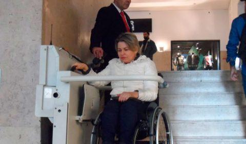 Mulher em uma cadeira de rodas utiliza uma plataforma elevatória para descer uma escada de seis degraus. Ao lado dela, um homem de paletó e gravata a auxilia.