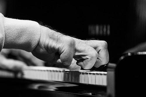 Foto em close da mão direita de um homem tocando piano, mostrando seus dedos com severas contrações
