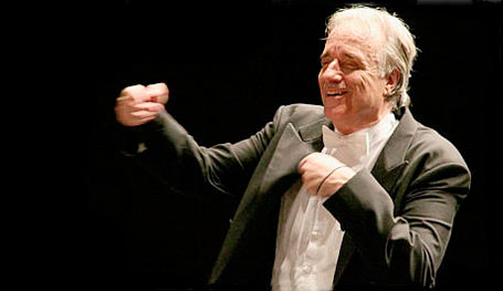 Foto horizontal de um maestro de meia idade, vestindo um fraque preto, gravata borboleta branca e com as mãos erguidas, conduzindo uma orquestra