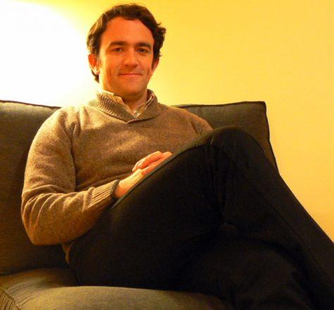 Foto quadrada de um homem sentado em um sofá, com a perna direita cruzada sobre a esquerda, as mãos cruzadas sobre a coxa direita e, ao fundo, uma parede amarela e o reflexo de uma luz no canto superior esquerdo