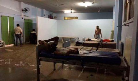 Foto horizontal de uma ala psiquiátrica de uma instituição para deficientes, mostrando um chão imundo, três camas em péssimas condições de higiene, um interno em pé próximo a uma das camas, dois outros deitados e um funcionário, de costas, do lado esquerdo