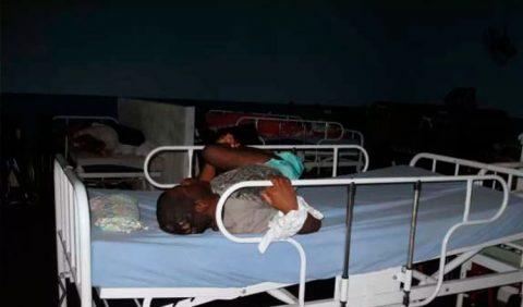 Foto horizontal, escura na parte de cima, mostrando um jovem amarrado no braço direito ao ferro de uma cama de hospital