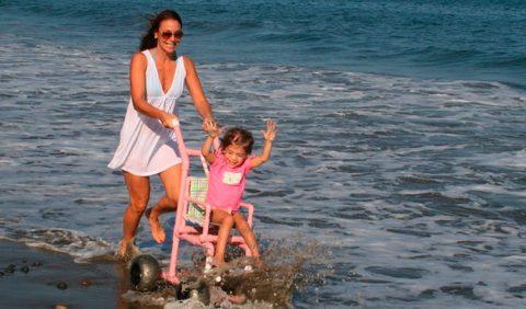 Foto horizontal da praia, mostrando o mar em grande escala e uma mãe empurrando uma cadeirinha de rodas cor de rosa com a filhinha pequena sentada nela e com os bracinhos erguidos, vibrando com o contato com a água.