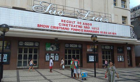 Foto horizontal da fachada do Cine São Luiz, em Fortaleza. Na placa, que vai de uma ponta a outra da foto, escrito São Luiz, em branco, e Secult 50 anos, Cineteatro São Luiz, Show Cristiano Pinho e Manasses 05/02 às 18h, em vermelho. Na calçada, pessoas caminham e um homem vende picolé