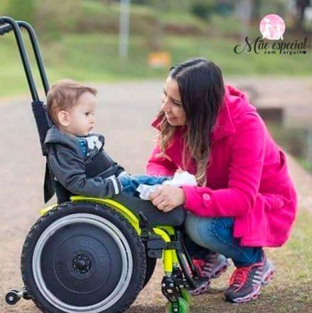 Mãe ajoelhada e sorrindo para seu filho em uma cadeira de rodas, de frente para ele. No alto, à direita, a logo do blog Mães Especiais com Orgulho