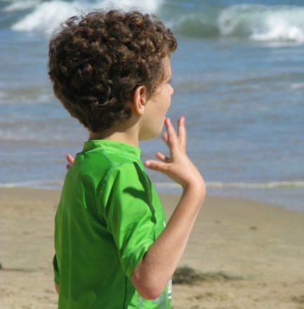 Foto quadrada, da cintura para cima, de um menininho autista, olhando para o mar. Ele veste uma camiseta verde e realiza o chamado flapping, movimento repetitivo com os braços.