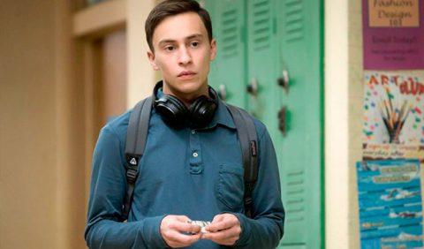 Foto horizontal de um rapaz, ao centro, com uma camisa azul de mangas compridas, um fone de ouvido no pescoço e uma mochila nas costas, em uma faculdade. Ao fundo, um armário verde desfocado e desenhos pregados nas paredes