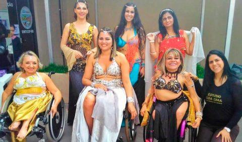 Foto horizontal de sete mulheres vestindo roupas típicas da dança do ventre. Atrás, três estão em pé. Em primeiro plano, três estão em cadeiras de rodas e, no canto direito, uma outra está ajoelhada e com uma roupa preta de academia.