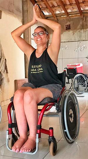 Foto vertical de uma mulher em uma cadeira de rodas, com as mãos postas acima da cabeça, realizando um movimento de dança