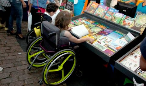 Foto horizontal com duas pessoas em cadeiras de rodas, em primeiro plano, de frente para uma estante com diversos livros. Ao redor delas, várias outras pessoas passeando pelos estandes