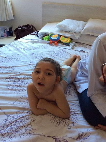 Foto vertical da pequena Alice, de sete anos, deitada de bruços na cama, com os bracinhos cruzados, olhando para a câmera. Ao seu lado, a metade de uma pessoa de sexo indefinido, de óculos, olhando para ela.