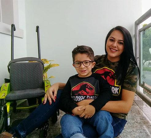 Foto quadrada de uma mãe com seu filho no colo, ambos usando uma camiseta do filme Jurassic Park. À esquerda, a cadeira de rodas do garoto.
