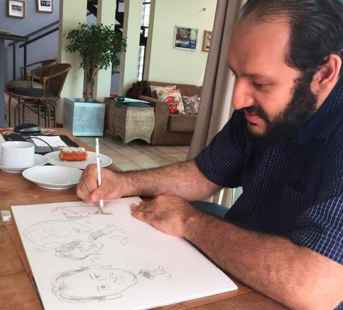 Homem de barba, de perfil, de frente a uma mesa, desenhando a lápis em uma folha grande de papel. Ao fundo, a sala da casa, uma xícara de café e um pedaço de bolo.