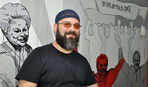 Foto de um homem vestido com uma blusa preta, um gorro azul escuro, óculos escuros, barba grisalha cheia, sorrindo, na frente de um painel cinza com desenhos de pessoas e da palavra DIRETAS JÁ! do lado direito, alto.