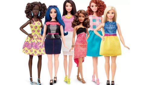 Seis bonecas Barbies, vestidas de formas diferentes e com tipos físicos diversos. À esquerda, uma boneca negra em um vestido amarelo florido; ao seu lado, uma boneca de cabelos azuis, saia azul escura e blusa listrada; no centro, uma boneca de cabelos negros, saia branca e blusa quadriculada em rosa e branco; ao lado, uma boneca baixinha, de cabelos castanhos ondulados e vestido vermelho e preto; a seguir, uma boneca de cabelos ruivos, cacheados, com saia azul turquesa e blusa quadriculada em azul, rosa e branco; por fim; uma Barbie loira, de saia amarela e blusa azul