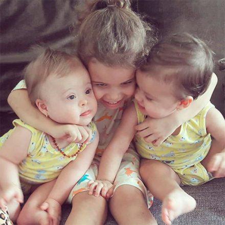 Três irmãs brincam e se abraçam afetuosamente. À esquerda, Luíza tem Síndrome de Down, é gêmea de Lívia, à direita. Ao centro, Laura, a mais velha