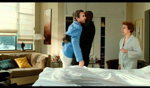 Foto horizontal em um quarto. Um homem negro carrega nos braços um outro homem, tetraplégico, para sua cadeira de rodas. Ao lado deles, uma enfermeira os observa.