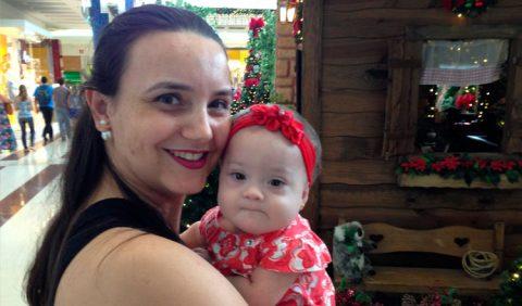 Mãe e bebê no colo passeando em um shopping center.