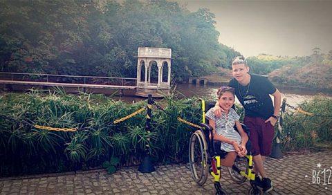 Jovem casal no canto direito da foto, ela em uma cadeira de rodas. Ao fundo, o Instituto Ricardo Brennand, em Recife.