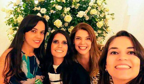 Quatro jovens mulheres na festa de colação de grau da Faculdade de Medicina. Ao fundo, uma coroa de flores