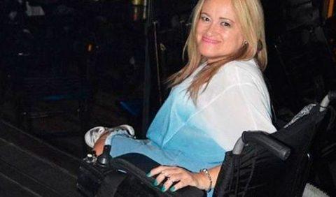 Mulher de meia idade, loira, em uma cadeira de rodas, sorrindo, fotografada de lado.