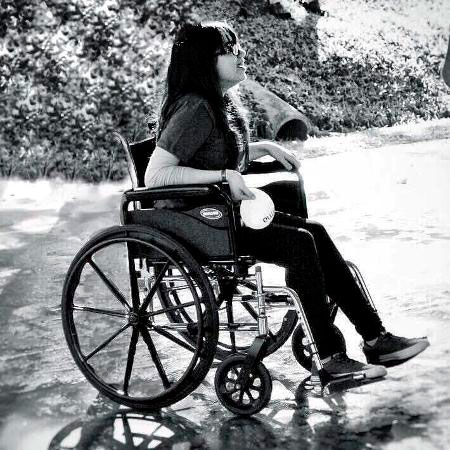 Foto em preto e branco de uma mulher em uma cadeira de rodas no que parece ser um parque.
