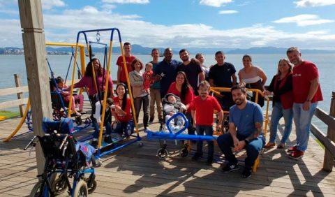 Grupo de cerca de vinte pessoas, entre homens e mulheres, adultos e crianças, com e sem deficiência, posam para a foto em um píer. Algumas crianças estão em brinquedos adaptados.