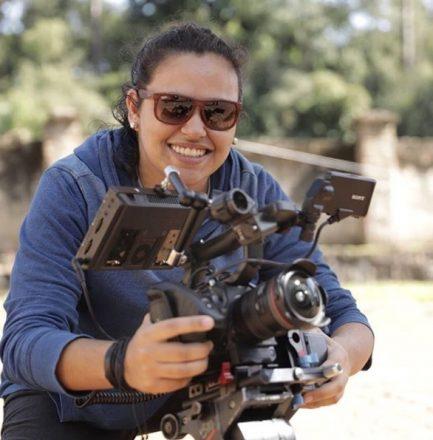 Mulher de óculos escuros, sorrindo, segura uma câmera de filmagem, de frente para a foto.